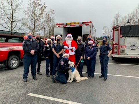 This is a picture of the firefighters, Santa, and Phoebe the Firedog in the Santa Parade.